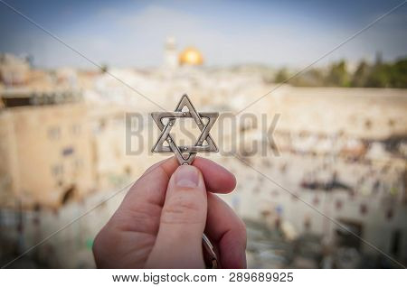Jerusalem, Israel. February 15, 2019. Hand Holding A Star Of David, A Jewish Religious Symbol Agains