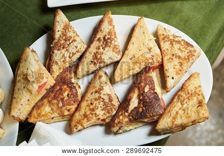Various Triangle Toasts Sandwiches On A White Plate, Close-up