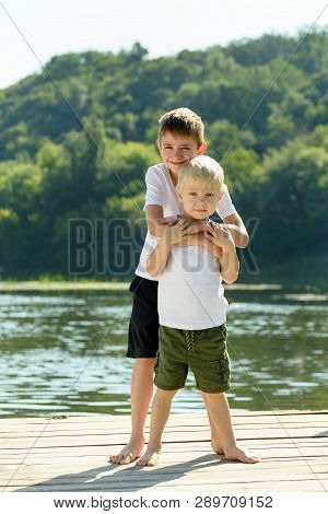 Two Little Boys Are Embracing On The Bank Of The River. Concept Of Friendship And Fraternity.
