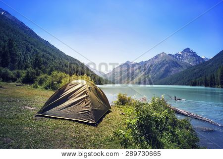 Camping Tent In Campground At National Park. Tourists Camped In The Woods On The Shore Of The Lake O