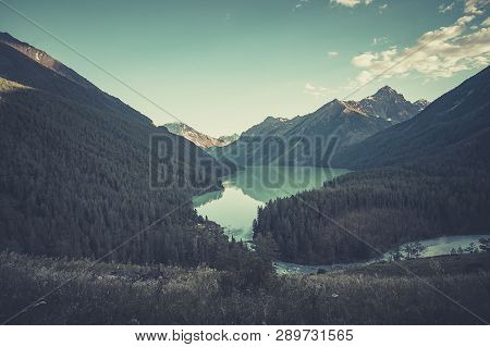 Russia, Altai, Mountains. Beautiful Blue Lake Kucherlinskoe In Foreground Against The Snow-capped Pe