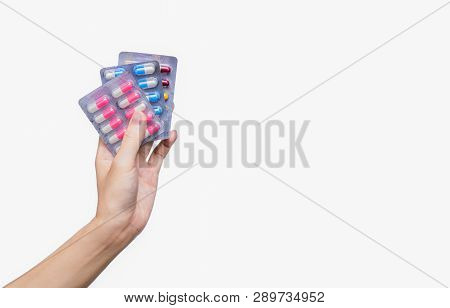 Asian Adult Hand Holding Antibiotics Drug In Blister Pack. Woman Hand Hold Three Pack Of Capsule Pil