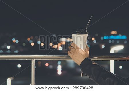 Womans Hand Holding Hot Cup Of Tea At Night With Bokeh City View. Glass Of Paper In The Hand Of A Yo