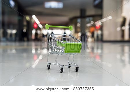 Little Shopping Trolley On Tile Floor Of Empty Shopping Centre. Concept Of Buying Things In Mall. To