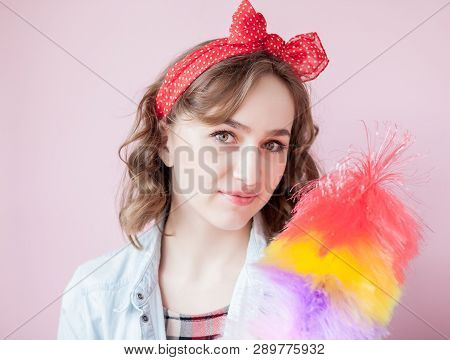 Cleaning pin up woman. Smiling pinup girl holds colorful duster brush. Cleaning service. Pin-up girl cleaner with feather duster. Retro woman with cleaning sweep. Selective focus on synthetic duster poster