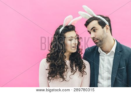 Young Pretty Pair Standing On Pink Background. At The Same Time, A Man Looks At A Loving Look At His