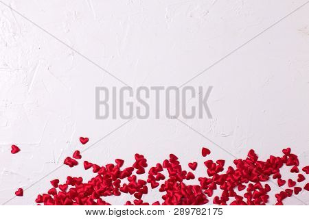 Border From Little Red Textilled Hearts  On  White Textured  Background.  Flat Lay. Place For Text.