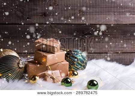 Stack Of Wrapped Presents, Golden And Green Balls And Fairy Lights On White Fur Background Against V