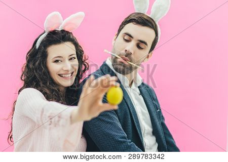 Young Couple On Pink Background. On The Head Is A Bunny Ears. The Wife Holds The Yellow Egg On The E