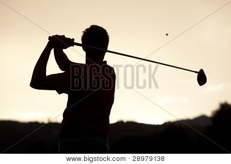 Silhouette of golf player teeing-off ball at sunset, view from behind.