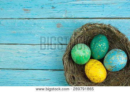 Happy Easter.colorful Shiny Eggs On Wooden Table Background. Wreath Woven From The Vines. Copy Space