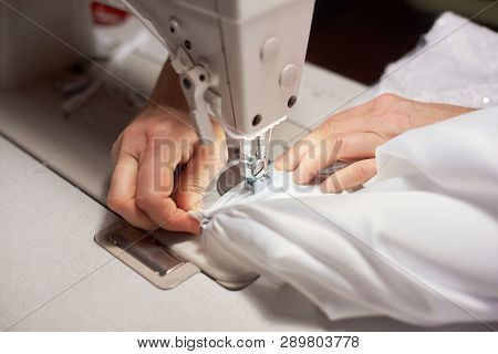 Female Hands Stitching White Fabric On Professional Manufacturing Machine At Workplace. Blurred Back