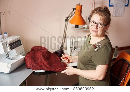 Happy clothier in glasses having break: sitting on her workplace in atelier, turning back, holding scissors and garment for repairing. Overlock machine, table lamp and threads on background. Side view poster
