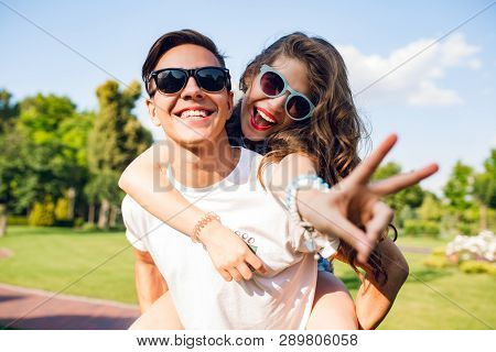 Portrait Of Cute Couple Having Fun In Park. Pretty Girl With Long Curly Hair Is Riding On Back Of Ha