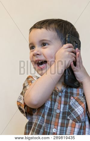 Cute Little Boy Talking By Mobile Phone On Light Background. Happy Little Boy Standing And Talking O