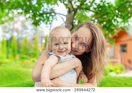 Beautiful Mother With Cute Little Baby Boy Having Fun Outdoors. Portrait Of Mom With Fun Child Smili