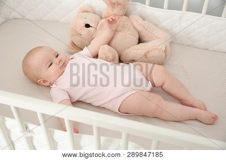 Cute baby girl with toy in crib. Bedtime schedule poster