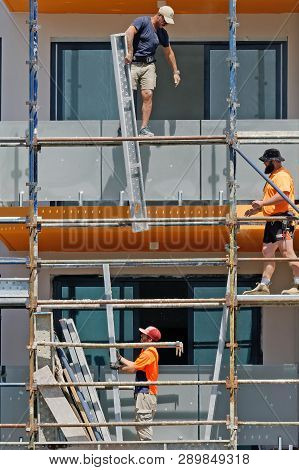 Gosford, New South Wales, Australia - March 4, 2019: Workmen Close Up, Dismantling Scaffolding And R