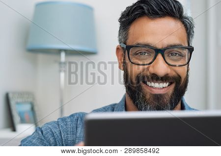 Closeup of businessman wearing glasses and working on laptop while looking at camera. Mature mixed race man relaxing at home with computer. Handsome hispanic man working at home and using laptop.