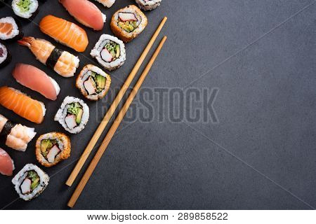 Top view of sushi with bamboo chopstick on black background. High angle view of corner of fresh uramaki, nigiri and hosomaki with copy space. Japanese food with fish rolls and spicy maki on slate.