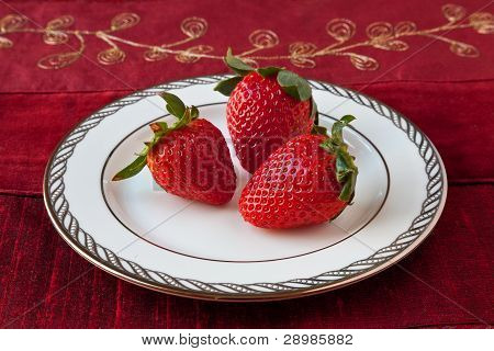 Three Strawberries On A Plate
