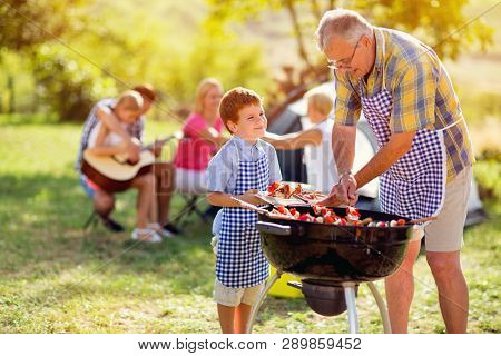 smiling grandfather giving grandson grilling meat for diner