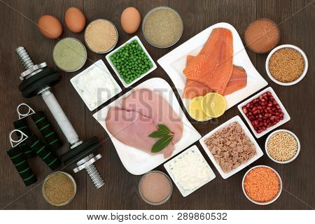 Body building dumbbell weights and hand grippers with high protein lean meat, fish and dairy, dietary supplement powders, vegetables, fruit and grains. Top view on oak wood table.