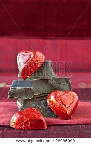 Candy Hearts On A Pile Of Dark Chocolate Pieces