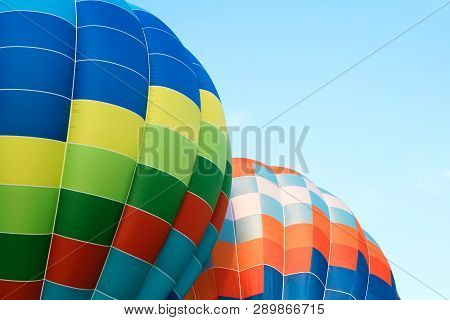 Closeup Of Two Multicolored Hot Air Balloons In The Blue Sky.