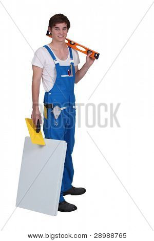Young tradesman posing with his tools and materials