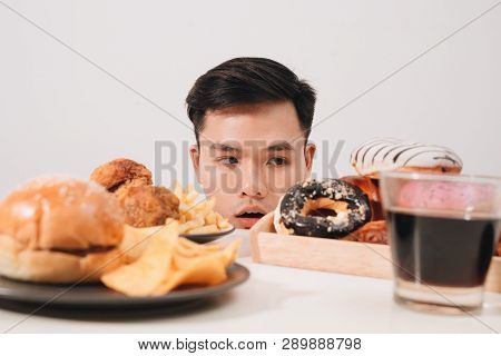 Young Man Having Cravings For Donuts, Hamburger, Chicken With Fries Instead