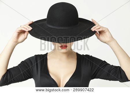 mysterious girl with red lipstick on her lips, in a black hat and dress with a neckline. studio photo on white background poster