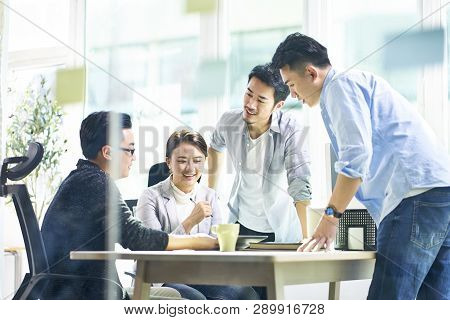 Group Of Four Happy Young Asian Corporate Executives Working Together Meeting In Office Discussing B