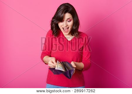 Girl With Purple Wallet Full Of Money In Hands Looks Astonished. Surprised Woman Wears Shirt, Holds