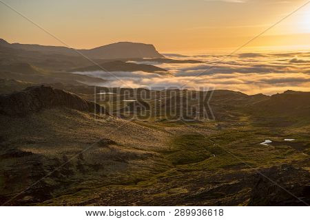 Dreamy misty landscape above the sea of clouds, mountains at sunset in Iceland poster