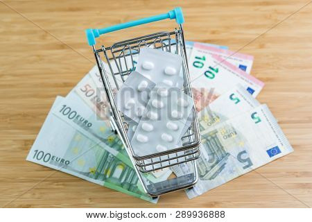 White Package Medicine Or Pills In Miniature Shopping Cart Or Trolley On Pile Of Euro Banknotes Mone