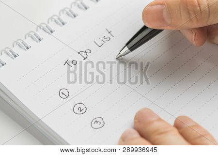 Hand Holding Pen Writing What To Do In Personal To Do List Note Pad On White Table Using As Task Lis