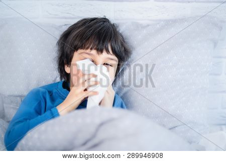 Little Child Boy Blow His Nose. Sick Child With Napkin In Bed. Allergic Kid, Flu Season. Kid With Co