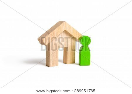 A Green Human Figure Stands Near The House On An Isolated Background. Concept Of Selling A Home, Buy