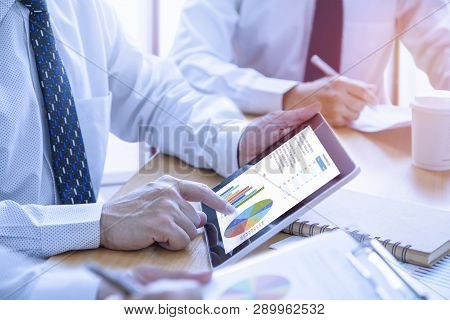 Businessmen Tab On Tablet Touch Screen To Deeply Reviewing A Diagram Or Chart And Financial Reports