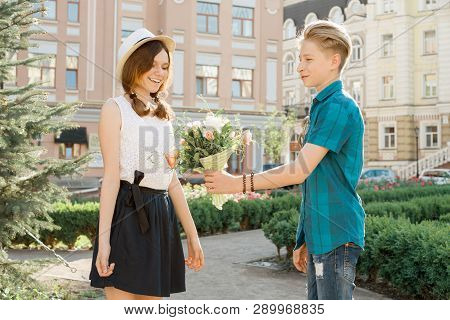 Teen Boy Congratulates Girl With Bouquet Of Flowers, Outdoor Portrait Couple Happy Youth.