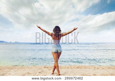 Freedom And Happiness Woman On Beach. She Is Enjoying Serene Ocean Nature During Travel Holidays Vac