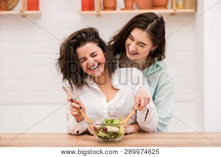 Two Young Women Cooking And Hugging At Kitchen.