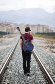 Young male musician walking with his acoustic guitar. poster