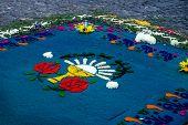 Blue sawdust alfombra with religious symbols for Semana Santa on cobbled street, Antigua, Guatemala poster