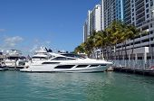 Luxury white motor yacht moored at a marina/condo complex in southeast Florida poster