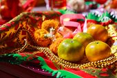 Orange Fruit, Rosary, Flower and Prayer Flag in Chinese Buddhist Temple, material offerings of traditional Mahayana Buddhist devotional practices for accumulation of merit. Religion and symbol concept poster
