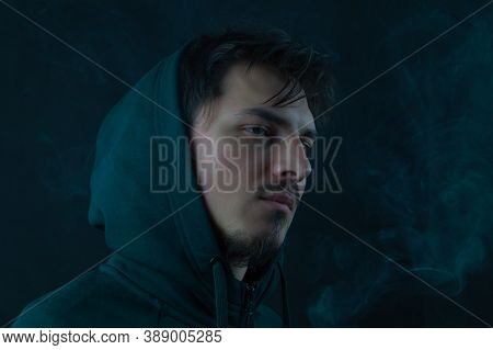 Young Man In The Hood On The Black Background. Male Portrait