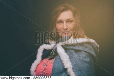 Woman In Queen Costume With Mantle. Artistic Fantasy Portrait Of Adult Woman In Royal Dress On Black