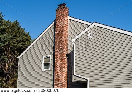 Side Of Older Style White House With Tall Red Brick Chimney Outdoor